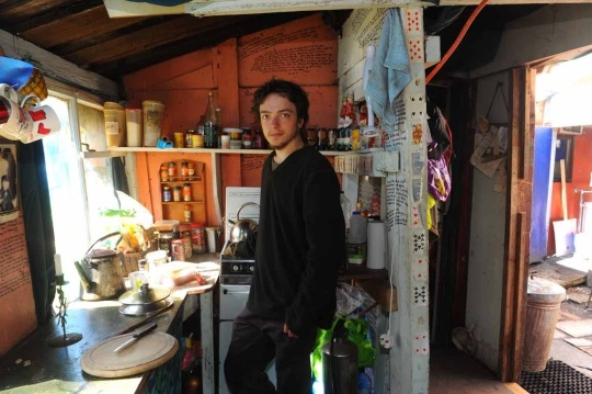 Angus Chalmers, a 20-year-old from Edinburgh and two year veteran of the camp, in the communal kitchen. A myriad of simple, hearty recipes are scrawled on the room's walls.