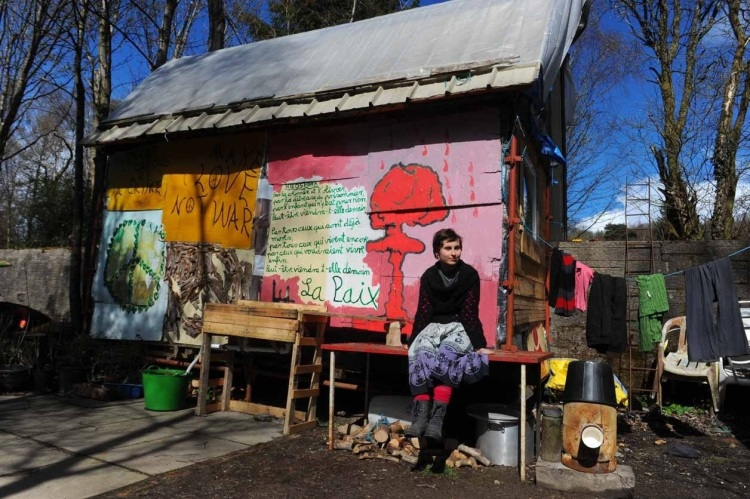 Julia Herzog, 23, from Mainz, outside her hut in the camp. She has painted the structure with her own artwork during her 18-month stay